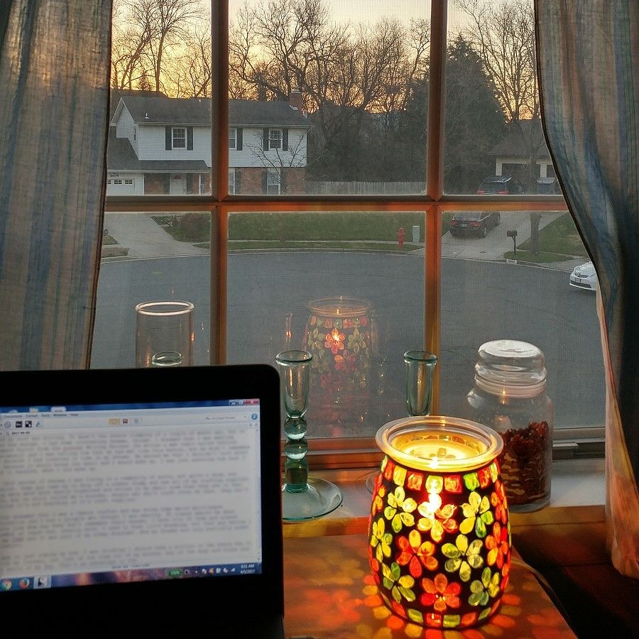 A laptop on a desk in front of a window showing a sunrise.